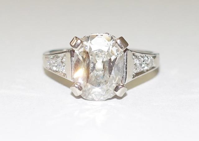 Bague en or gris centrée d'un diamant taille ovale facettée environ