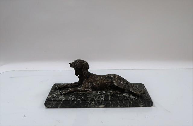 Chien allongé. Sculpture en bronze à patine nuancée, socle en marbre