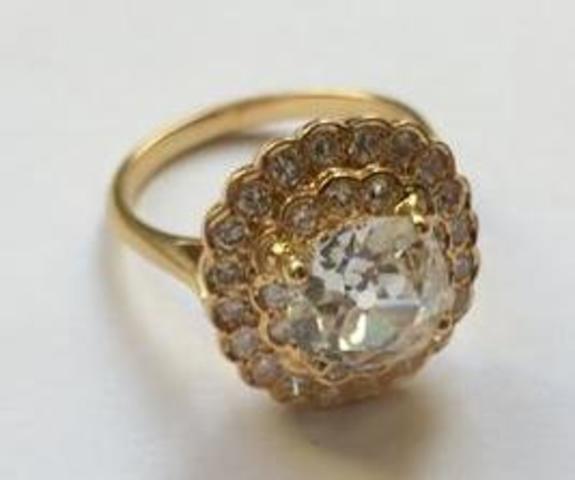 Une bague en or jaune 750/1000ème, sertie d'un diamant central taille