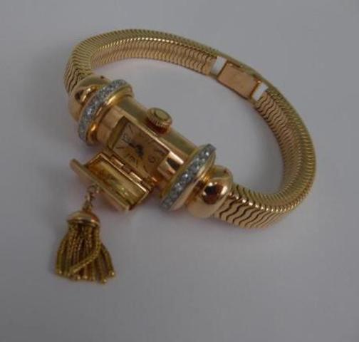 Bracelet en or maille tubogaz, découvrant au centre une montre, ceinturée