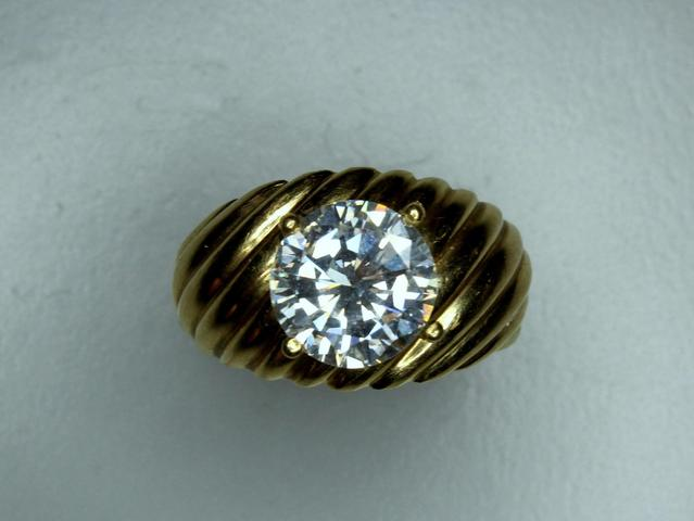 BAGUE ORNEE D'UN BRILLANT SUR UN JONC LARGE EN OR JAUNE GODRONNE,