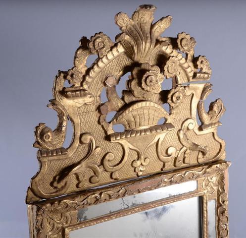 Glace à pareclose en bois doré à décor de fleurs et dauphins,